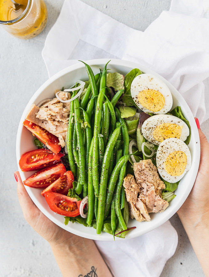 hands holding bowl of nicoise salad with hard boiled eggs