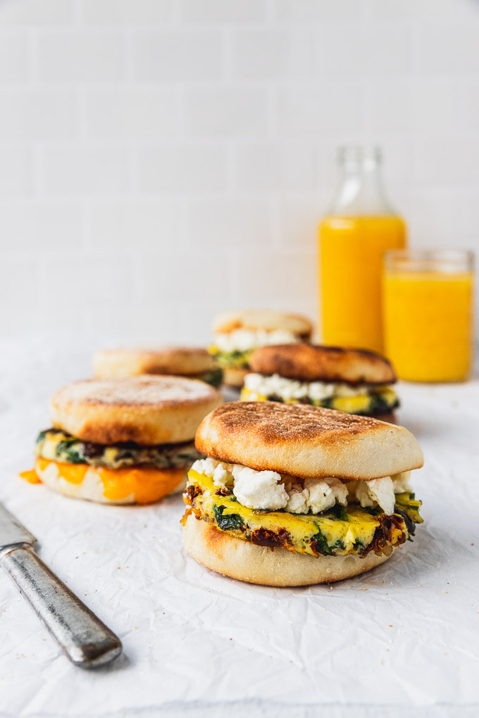 rows of breakfast sandwiches with knife and orange juice glasses