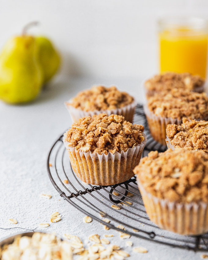 muffins on cooling rack with oats and whole pear