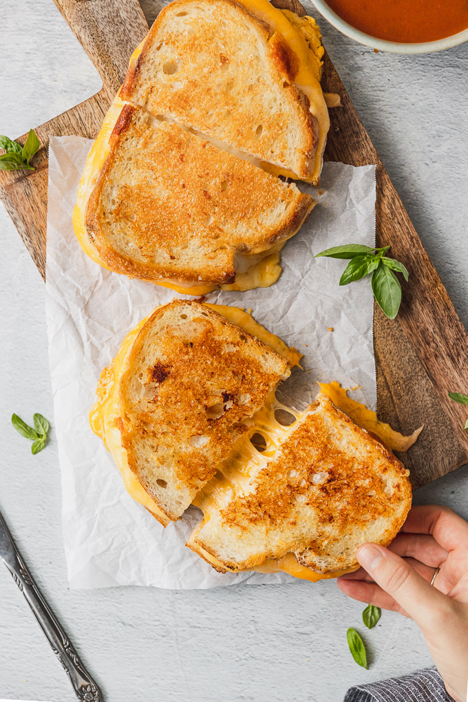 Hand pulling grilled cheese slice.