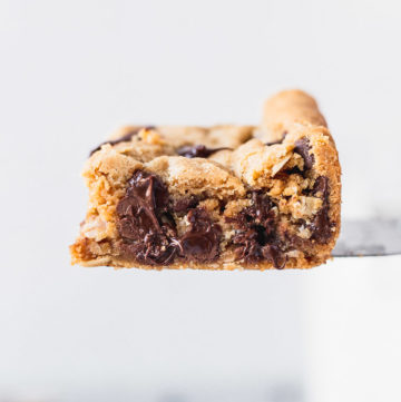 server holding up a chocolate chip peanut butter cookie bar
