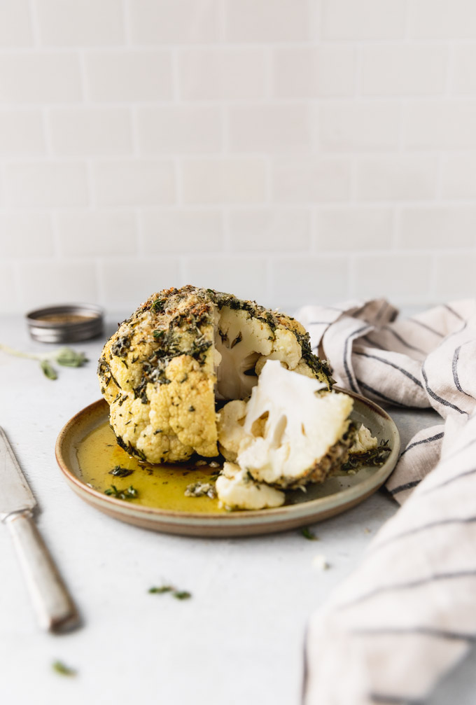 whole roasted cauliflower on plate cut