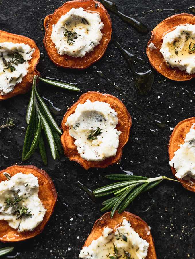 overhead sweet potato rounds on black serving tray next to rosemary sprigs
