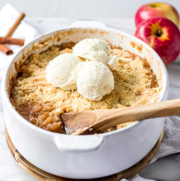 Baking dish with apple crisp topped with ice cream and a spoon scooping.