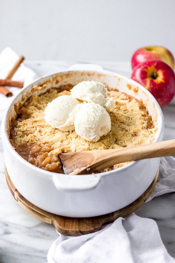 white pan with apple crisp and ice cream and wooden spoon scooping out