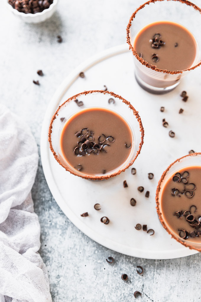 overhead look of three chocolate drinks with chocolate swirled garnish on white tray next to white linen