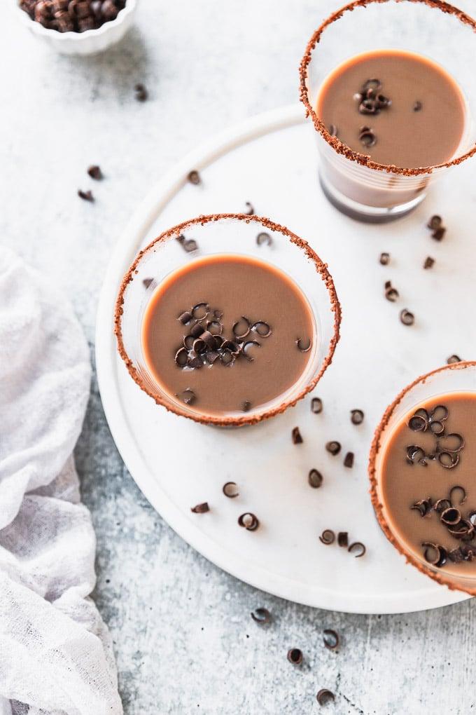 overhead look of three chocolate drinks with chocolate swirled garnish on white tray next to white linen