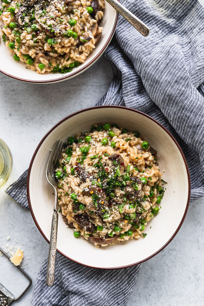 Two bowls of mushroom risotto with forks next to blue striped linen and wine glass.