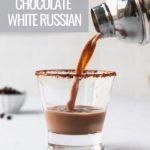 Pouring white russian into a cocoa rimmed martini glass from shaker