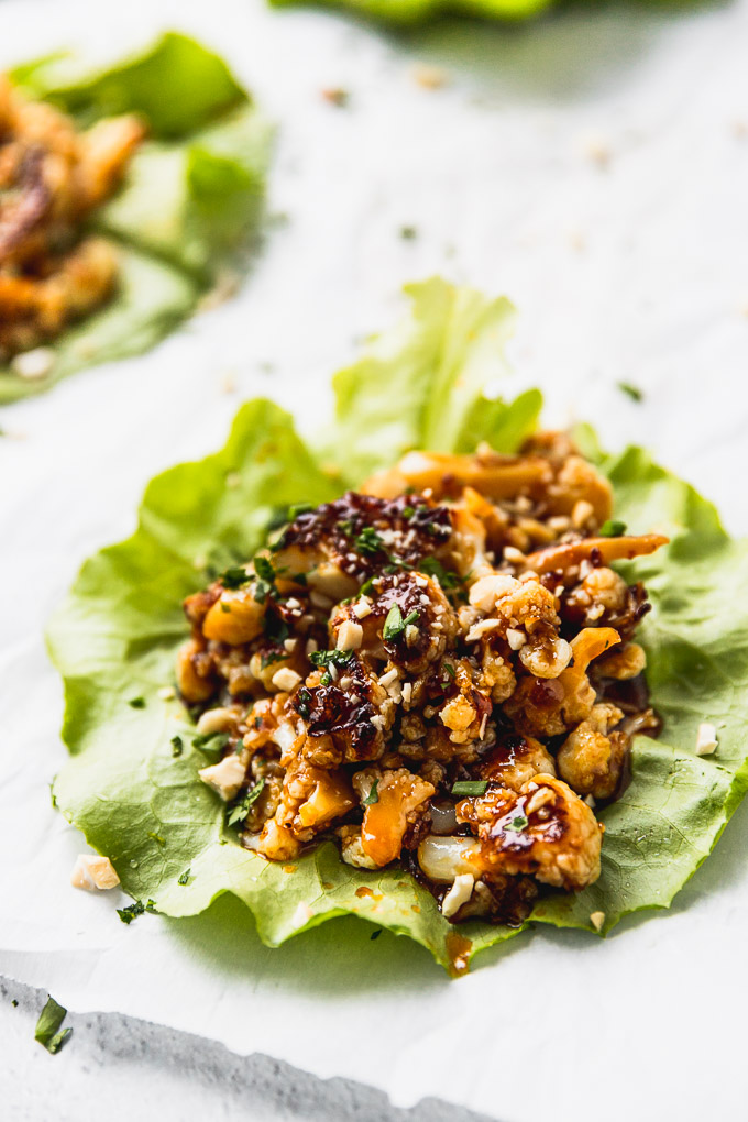 up close lettuce wrap with cauliflower on white background with teriyaki sauce