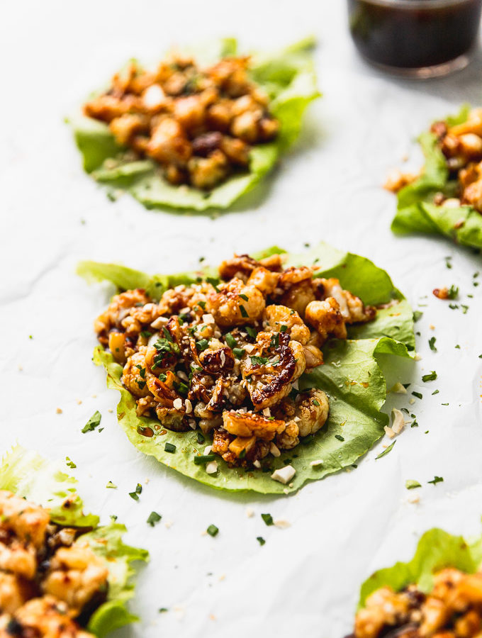 five lettuce wraps with cauliflower on white background with teriyaki sauce