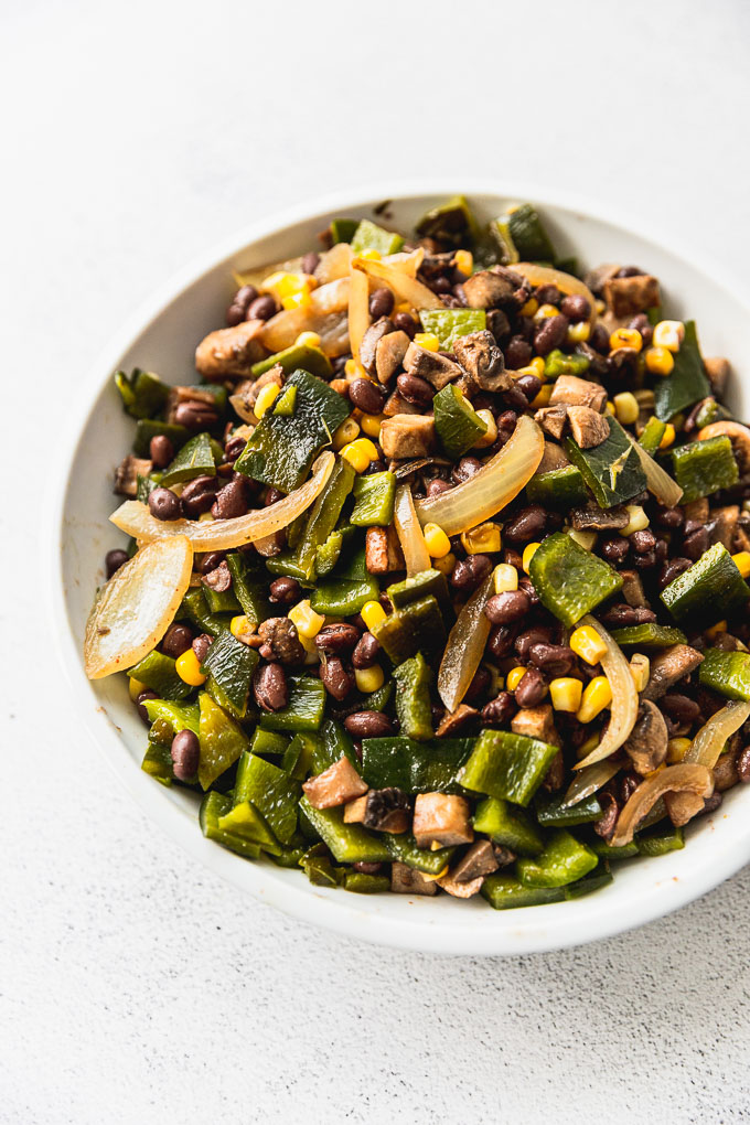 bowl of taco filling with poblano peppers, onion, mushrooms, black beans, and corn