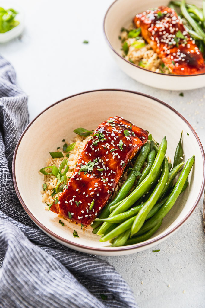 two bowls of teriyaki salmon with rice and green beans