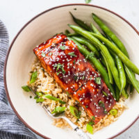 bowl with rice, green onions, teriyaki salmon, and fresh green beans next to blue linen