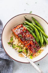 Bowl with rice, green onions, teriyaki salmon, and fresh green beans next to blue linen.