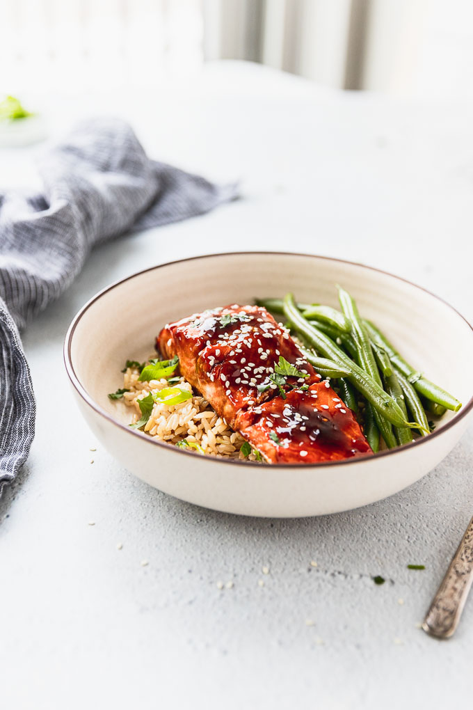 one bowl of teriyaki salmon with green beans next to linen and fork