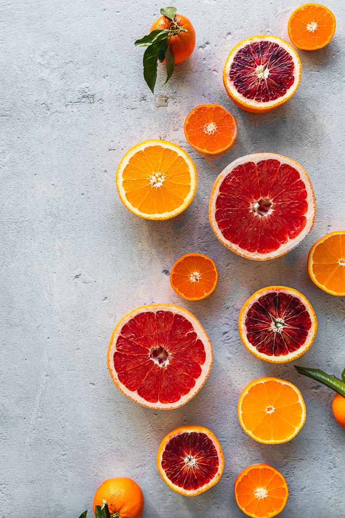 Citrus lined up across the right half of the frame cut in half