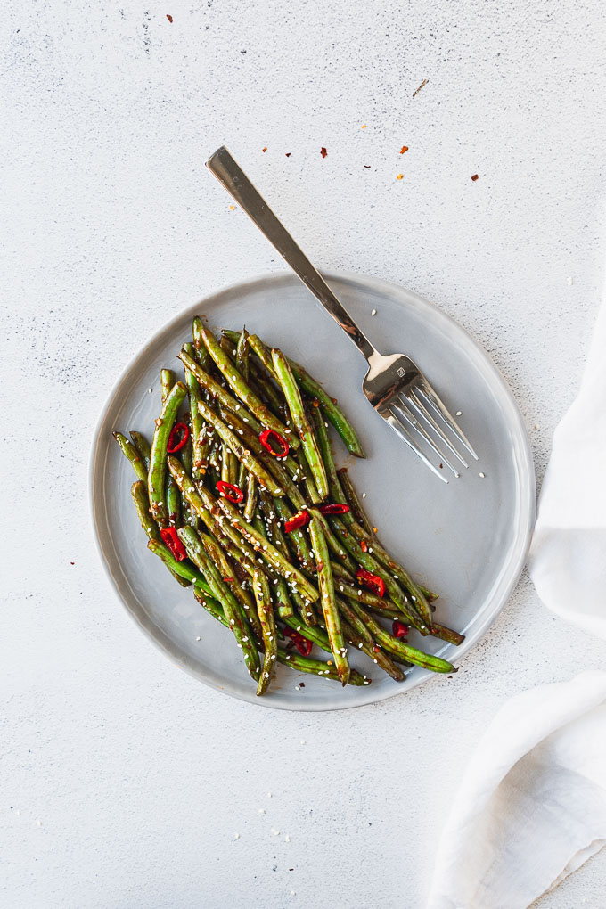 overhead view of gray plate with large fork with asian green beans