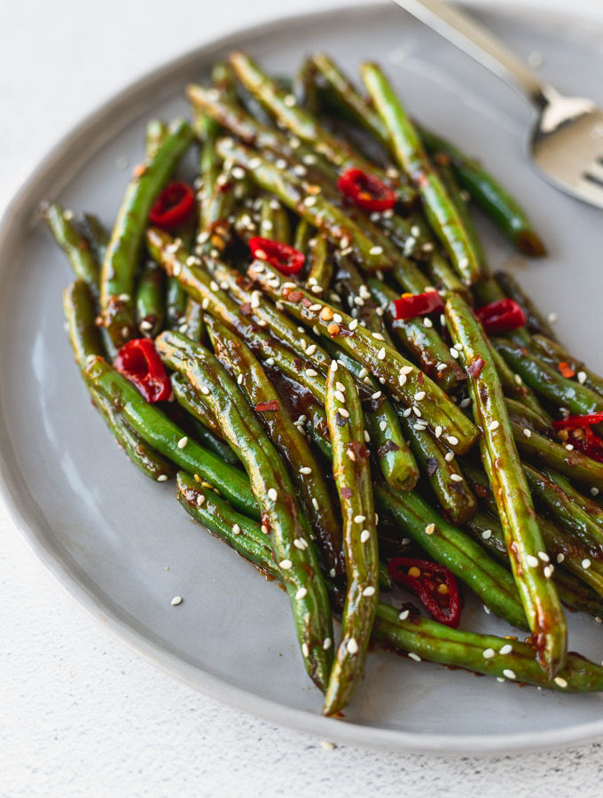 gray plate with green beans covered with soy sauce and red chilis