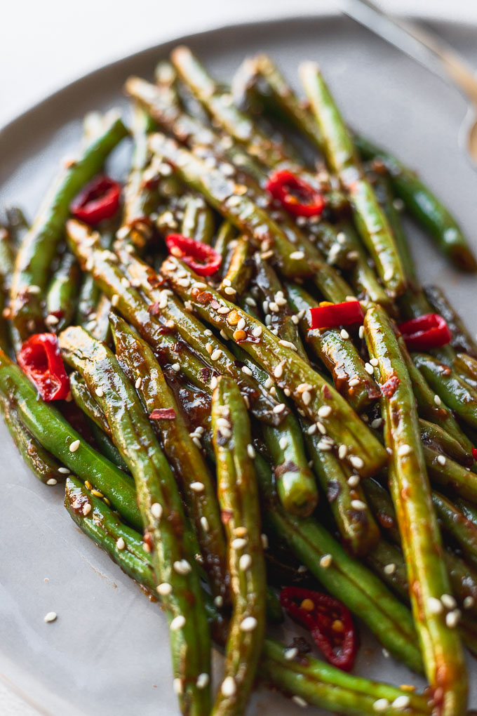 up close view of asian green beans on gray plate next to fork