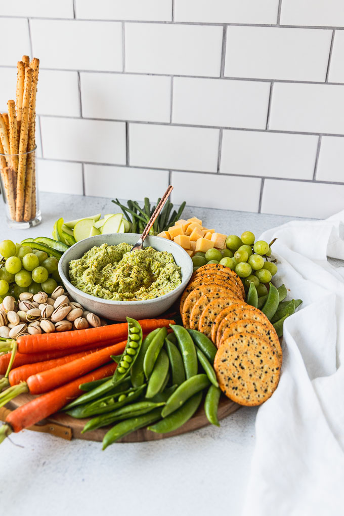side view of snack board with edamame hummus