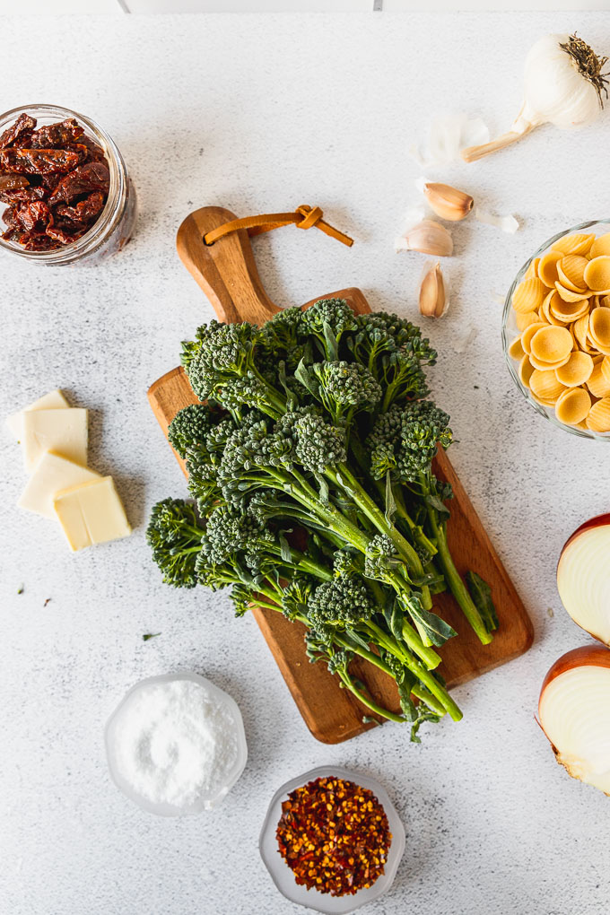 broccolini on wooden tray next to butter, pasta, sun dried tomatoes, garlic, and onion for the pasta ingredients