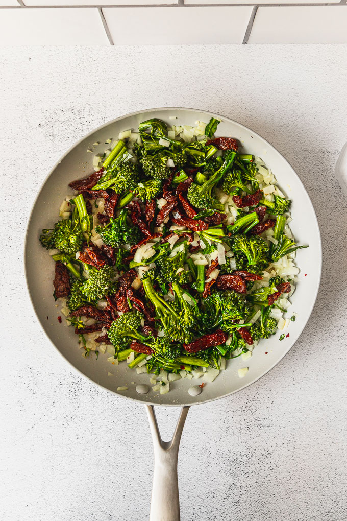 broccolini, sun dried tomatoes, and onion in skillet