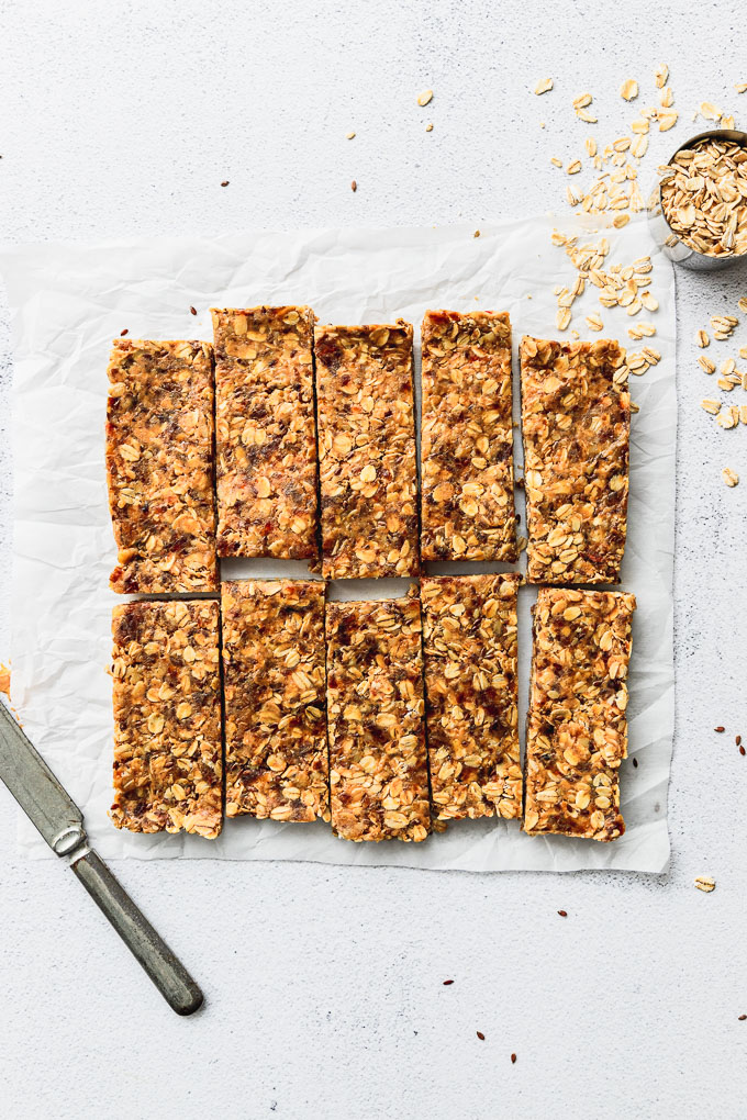 cut granola bars spread on parchment paper next to knife