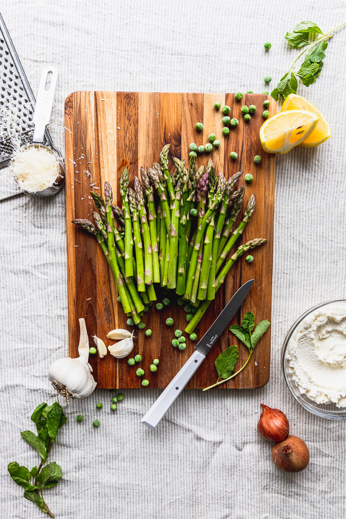 asparagus on cutting board with parmesan, peas, lemon, garlic, and ricotta around it
