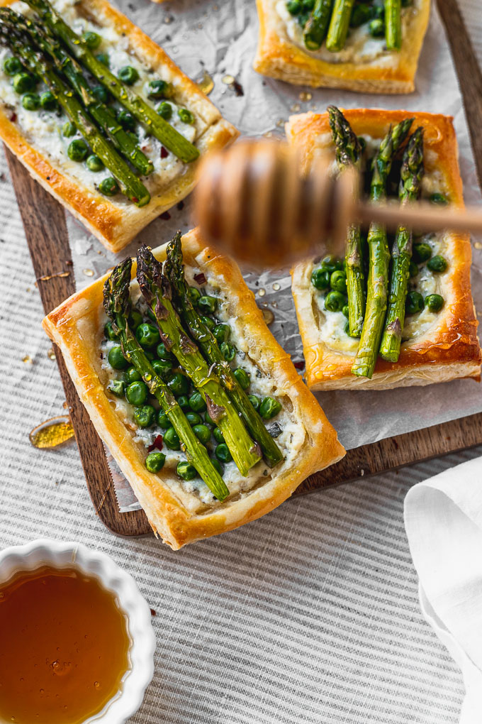 drizzling honey on asparagus pea tarts