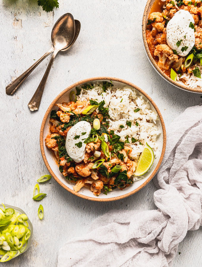 overhead view of two white bowls with exposed rims filled with cauliflower curry topped with sour cream and green onions next to gray linen and spoons