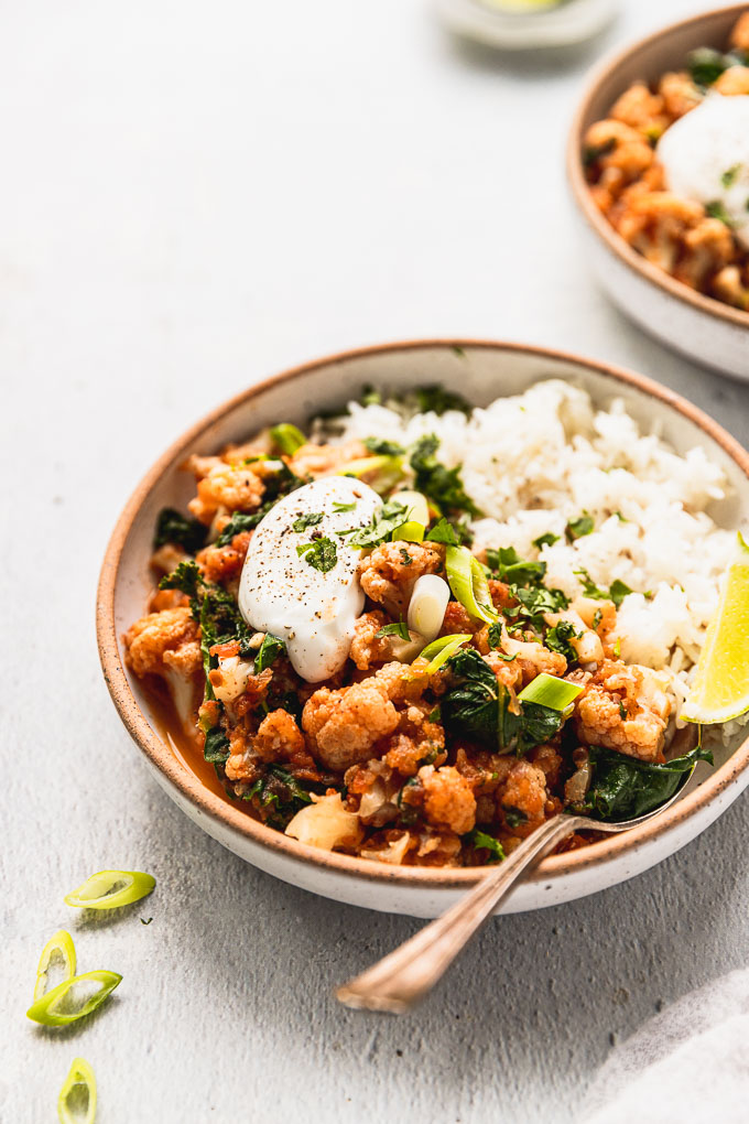 white bowl with exposed rim with cauliflower kale curry next to white rice and lime wedge topped with sour cream, pepper and green onion