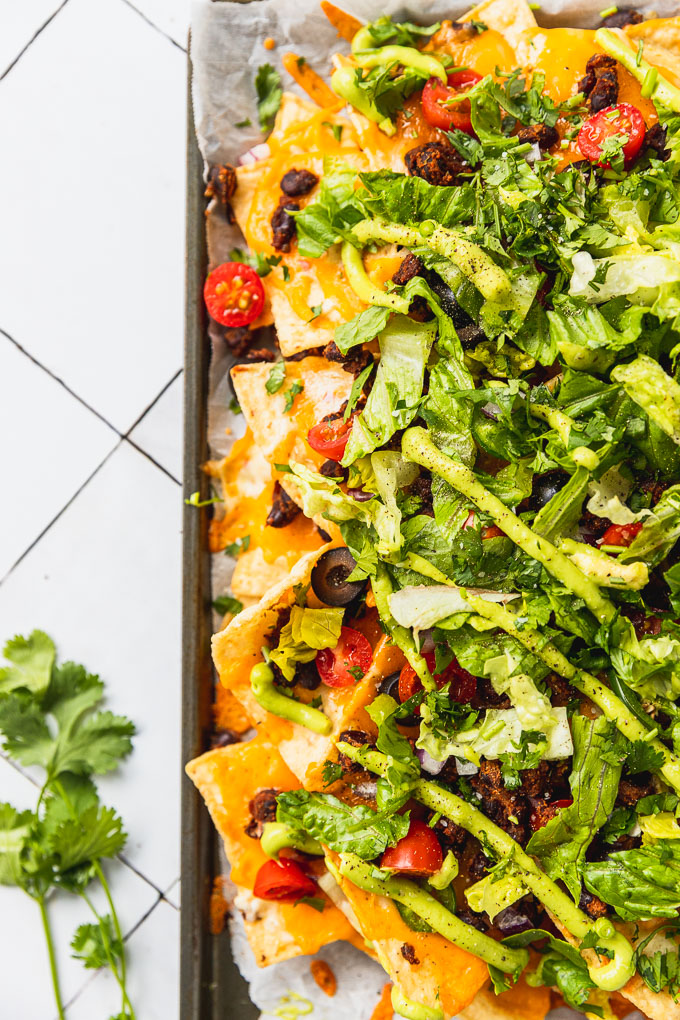 up close view of nachos on sheet pan with cheese, lettuce, tomatoes, olives, and avocado sauce