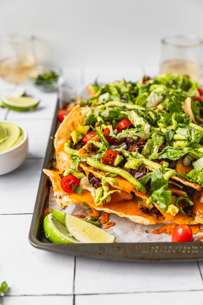 sheet pan with tortilla chip nachos, black beans, and lettuce with lime wedges and wine in the background