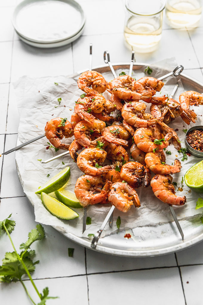 side angle of silver tray with parchment paper with shrimp skewers piled on top of each other next to lime wedges and red pepper flakes