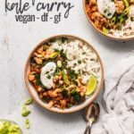 bowl of cauliflower kale curry overhead with spoons next to it