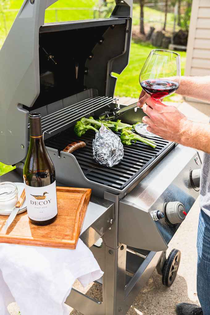 open grill with foil packet, brat, and broccoli. person grilling is holding a wine glass and tongs are moving broccoli.