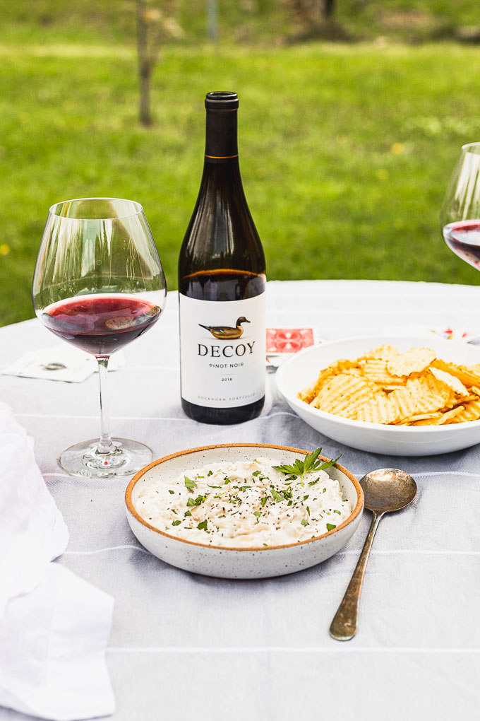 table with a bowl of onion dip and a spoon next to it, potato chips, a bottle of wine and red wine glasses. cards scattered around with grass in the background.