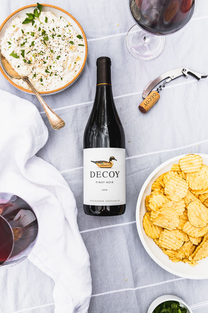 overhead view of bottle of decoy wine  in center next to a bowl of onion dip, wine glass, white linen, and potato chips