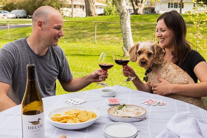 guy and girl cheersing with red wine at a table with cards, potato chips, dip, and wine bottle; girl has puppy in lap.