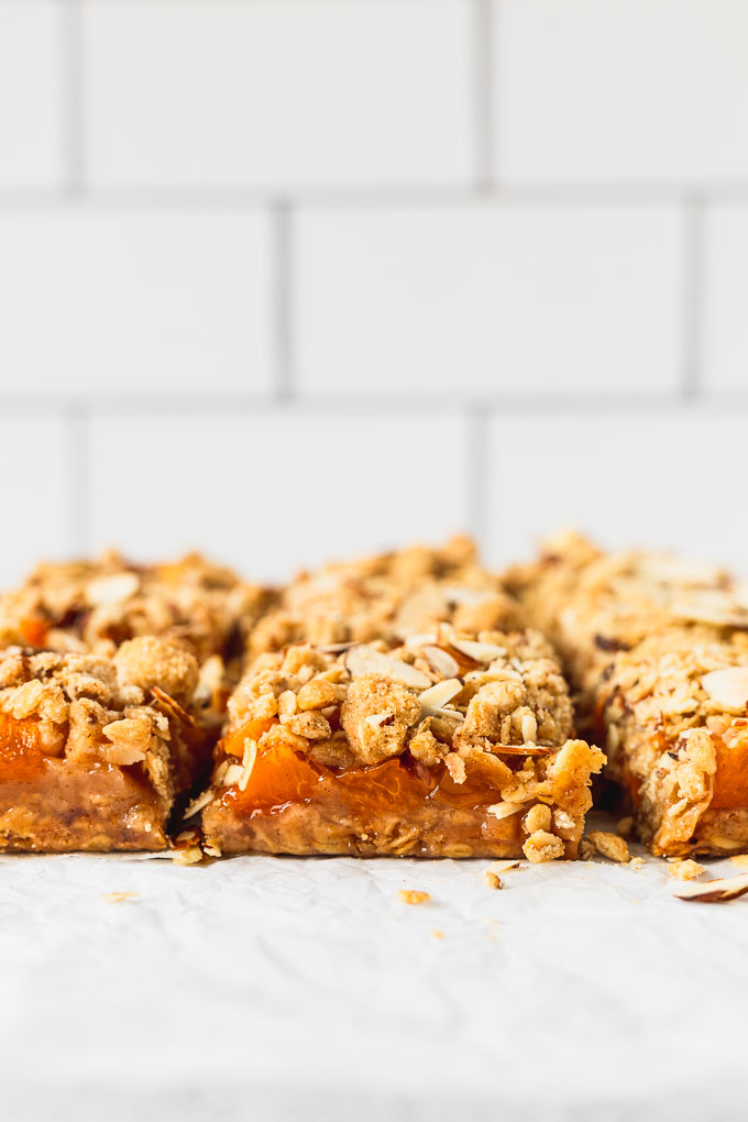 side view of sliced apricot almond crumble bars next to each other with white subway tile in background