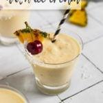 glass of a pina colada milkshake with cherry garnish and straw