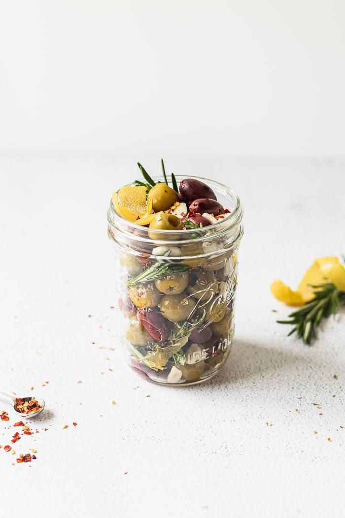 jar with olives, rosemary, garlic, and lemon