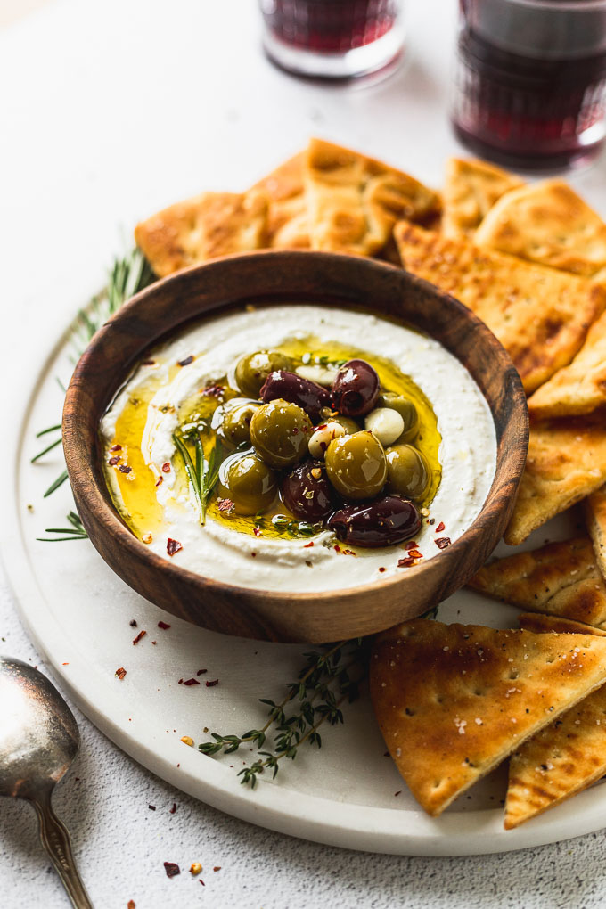 side view of feta in a bowl with olives and pita chips