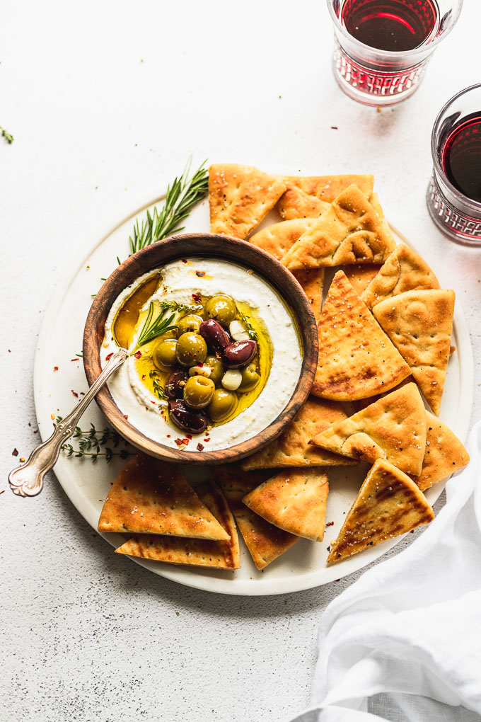 marble serving tray with pita chips and a wooden bowl of whipped feta topped with marinated olives and a spoon inside