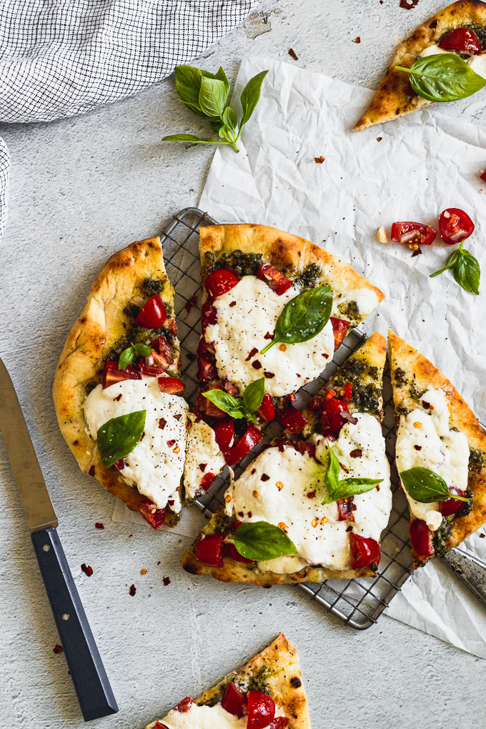 naan flatbread pizza on cooling rack next to knife