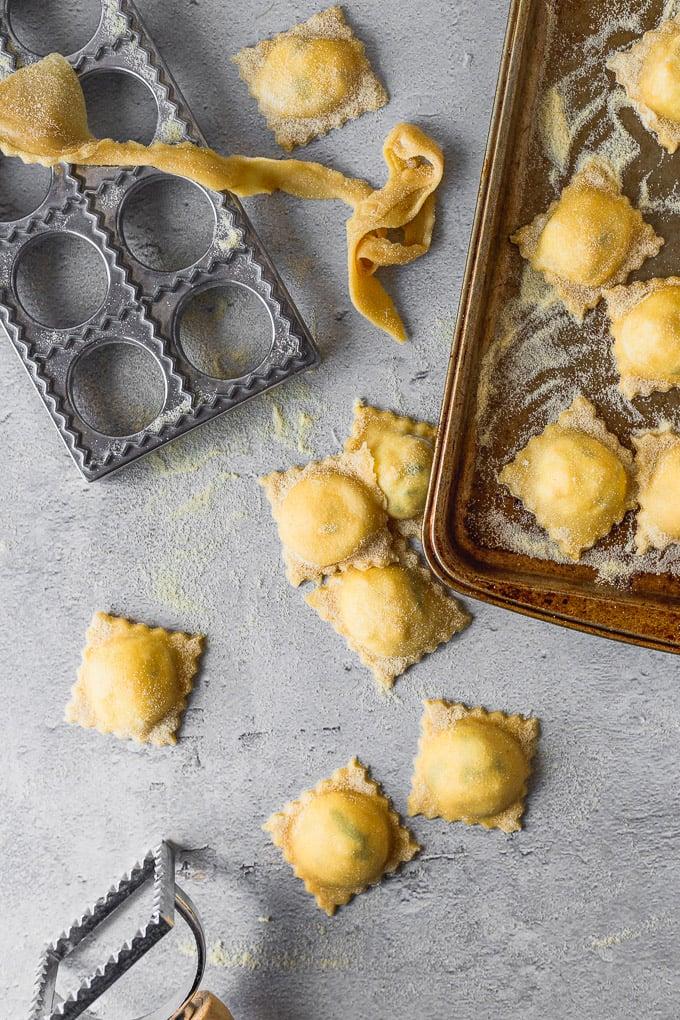 fresh pasta dough cut into ravioli on baking sheet