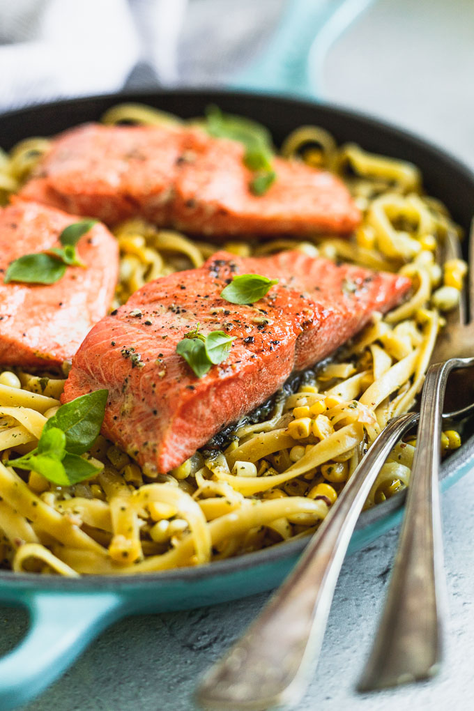 skillet with pesto pasta topped with salmon filets and serving fork next to it