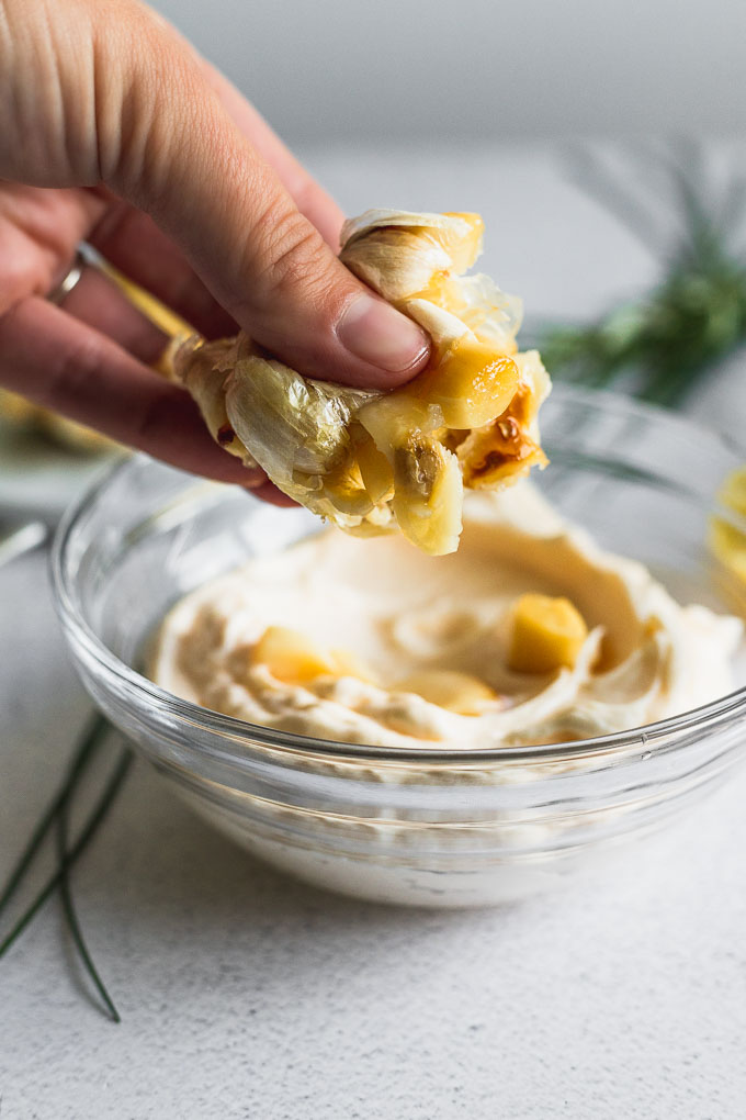 hand squeezing garlic cloves into bowl of mayonnaise
