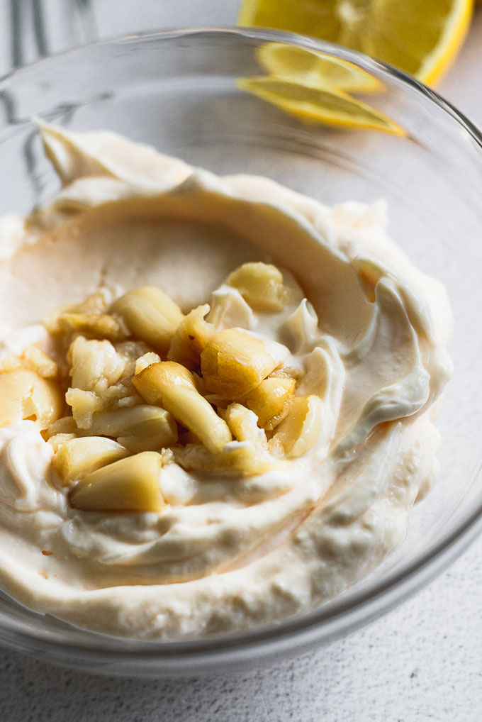 bowl of mayonnaise with roasted garlic cloves